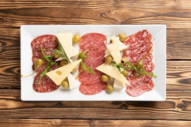 薄くスライスしたサラミソーセージとチーズ、オリーブ、ケッパー、ルッコラの盛り合わせ
