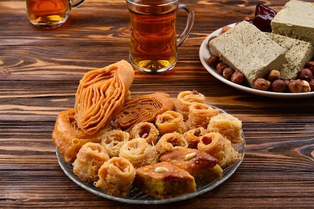 나무 배경에 차와 함께 모듬된 전통적인 동부 디저트. 나무 테이블에 아라비아 과자입니다. 접시에 바클라바, 할바, 라하트 로쿰, 셔벗, 견과류, 날짜, 카다이프. 텍스트를 위한 공간입니다.