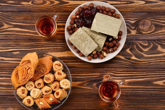Ассорти из традиционных восточных десертов с чаем на деревянных фоне. арабские сладости на деревянном столе. пахлава, халва, рахат лукум, шербет, орехи, финики, кадаиф на тарелках. место для текста.