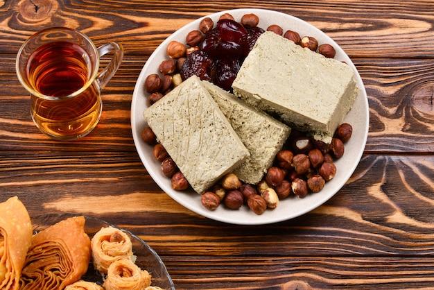 木製の背景にお茶と伝統的な東部のデザートの盛り合わせ。木製のテーブルにアラビアのお菓子。