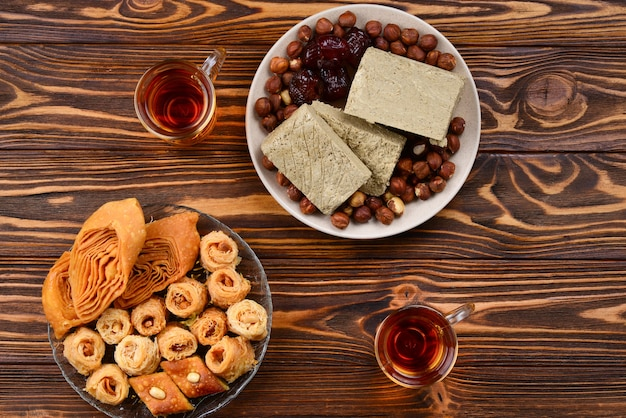 Assorted traditional eastern desserts with tea on wooden background. arabian sweets on wooden table. baklava, halva, rahat lokum, sherbet, nuts, dates, kadayif on plates. space for text.