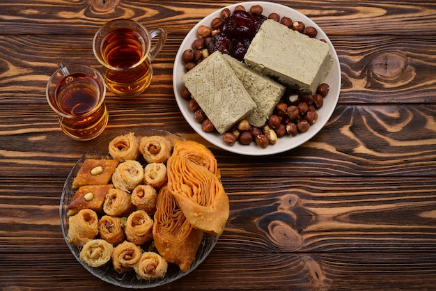 Assorted traditional eastern desserts with tea on wooden