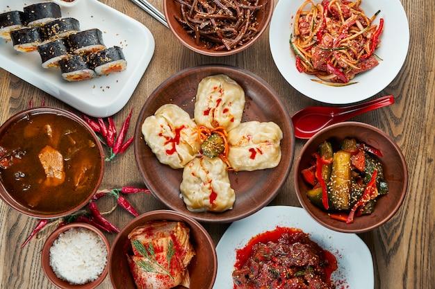 Ассорти традиционных корейских блюд - кимчи, рулеты гимбап, вареные на пару пельмени (манду) на деревянной поверхности. вид сверху, плоская кладка еды. корейская кухня