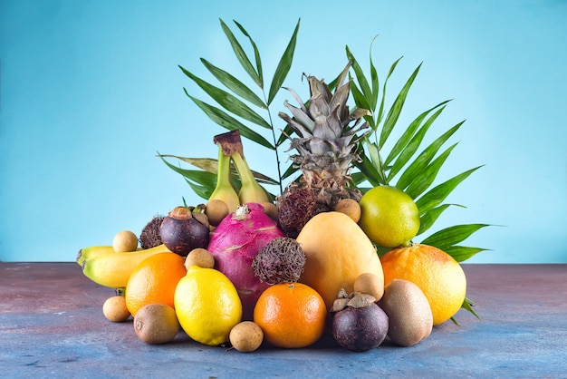 Assorted tropical fruits, orange,ananas or pineapple, lime,mango, dragon fruit, orange, banan, rambutan and lichi on blue background.