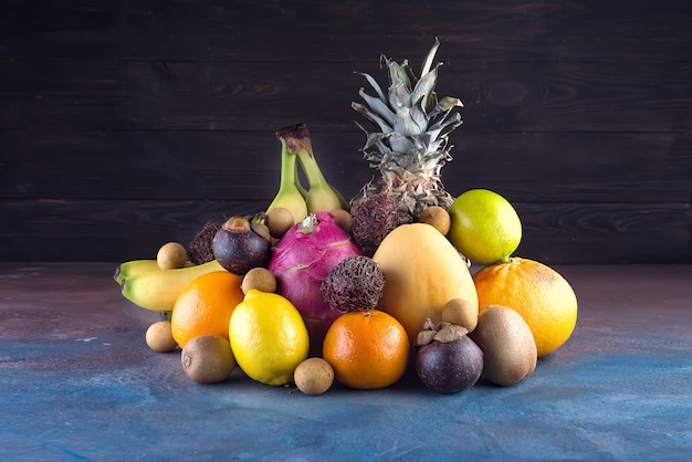 Assorted tropical fruits, orange,ananas or pineapple, lime,mango, dragon fruit, orange, banan, rambutan and lichi on dark background.