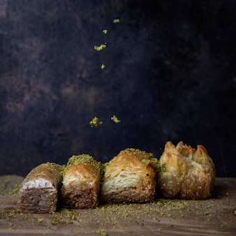 Assorted turkish baklava with ground pistachios in wooden plate