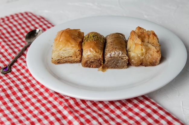 Assorted turkish baklava with spoon and rag in round plate