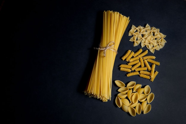 Assorted types of pasta on black background. top view. various forms of pasta. copy space for design.