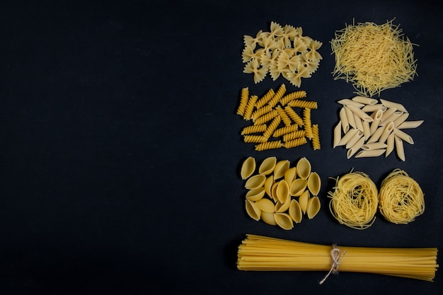 Assorted types of pasta on black background. top view. various forms of pasta.