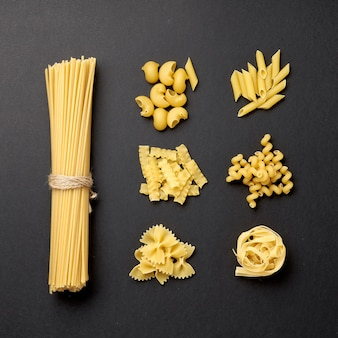 Assorted types of pasta on black background