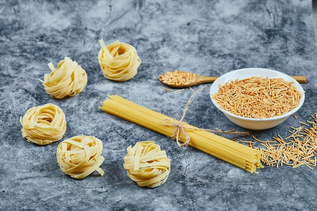 Assorted uncooked pasta with a wooden spoon.