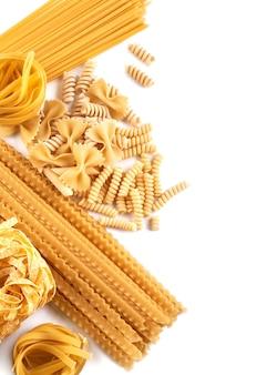 Ассорти из макаронных обоев. смешайте макароны, спагетти на белом фоне с копией пространства