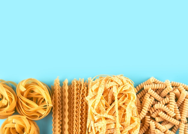 Assorted varieties of pasta wallpaper. mix macaroni, spaghetti on blue background with copy space