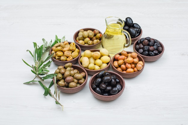 Assorted variety of olives in a clay bowls with olive leaves and a jar of olive oil high angle view on white wood