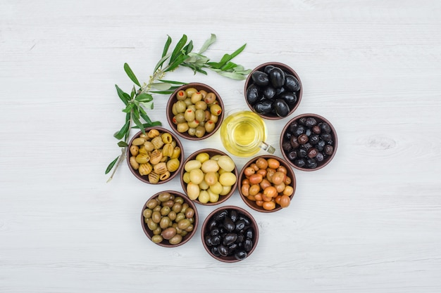 Assorted variety of olives in a clay bowls with olive leaves and a jar of olive oil top view on white wood