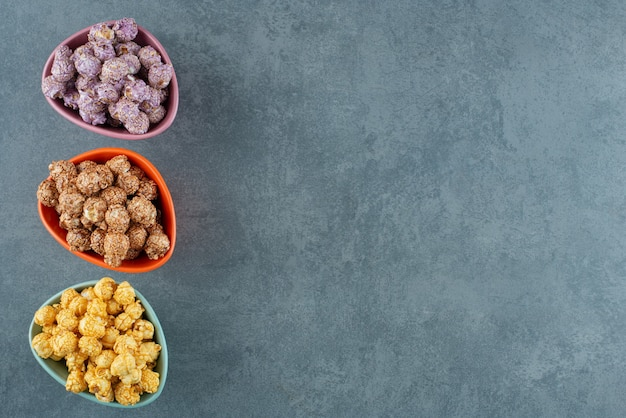 Una varietà assortita di colori di caramelle popcorn assortiti in piccole ciotole su sfondo marmo. foto di alta qualità