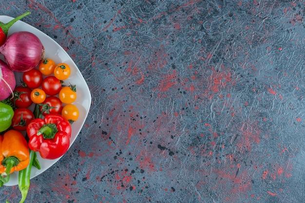 大理石の背景に、皿に野菜の盛り合わせ。