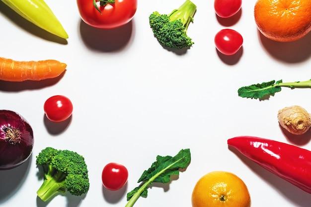 Ассорти из овощей и фруктов на белой поверхности.