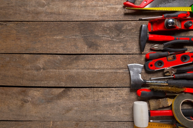 Assorted work tools on wood background