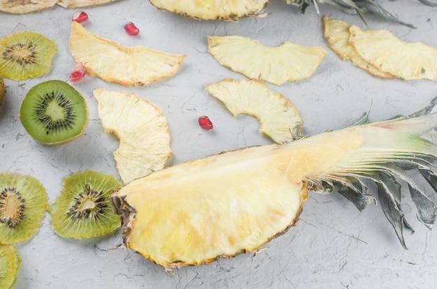 회색 배경에 모듬된 말린 칩과 익은 과일. 과일 칩. 건강한 식생활 개념, 간식, 설탕 없음. 상위 뷰, 복사 공간입니다.