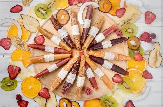 Ассорти сушеных чипсов и спелых фруктов на сером фоне
