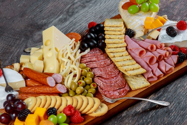 Assortment of appetizers: different sorts of cheese, crackers, grapes, nuts,