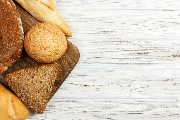 Assortment of baked bread on white wooden table