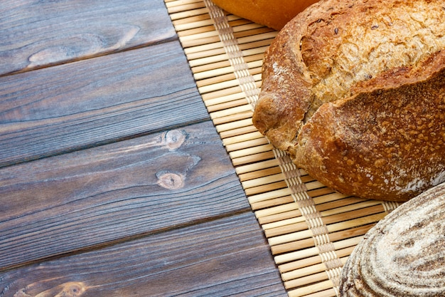 Assortment of baked bread on wood table. top view with copy space