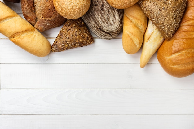 Assortment of baked bread on wooden table background.