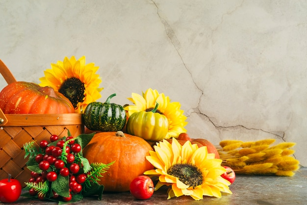 Assortment of berries with pumpkins and flowers