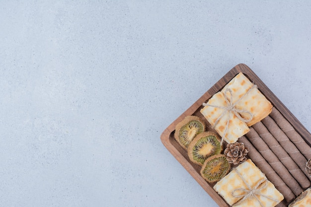 Assortimento di biscotti e kiwi secchi su tavola di legno.