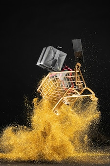 Assortment of black friday gifts in shopping cart with golden glitter