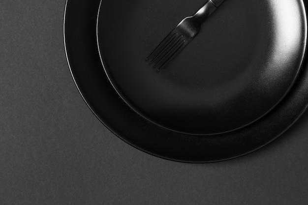 Assortment of black plates on black background