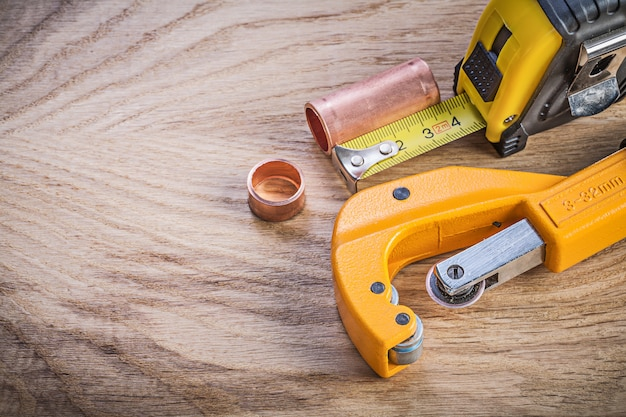 Assortment of brass water pipe cutter measuring tape on wood board plumbing concept