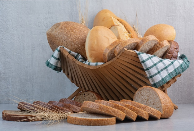 Assortment of bread in basket on marble surface