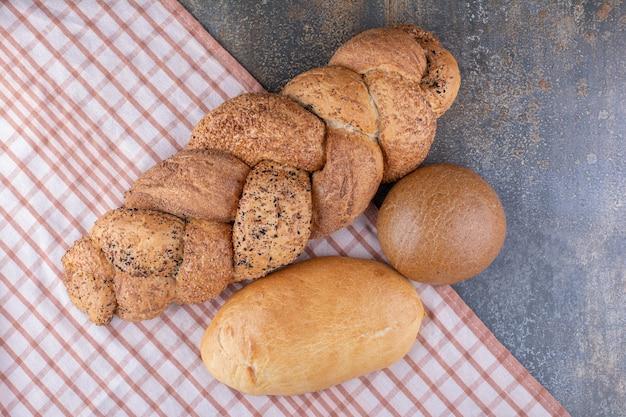 Assortimento di pagnotte di pane su una tovaglia sulla superficie in marmo
