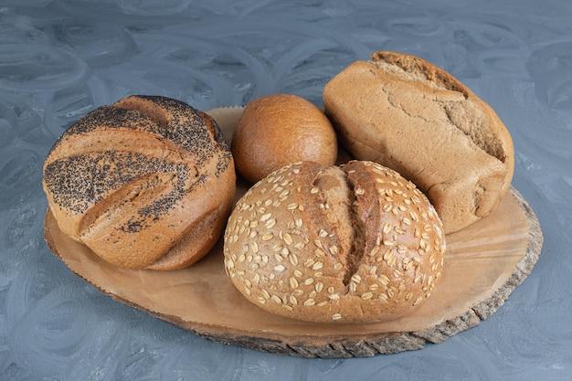Assortimento di pagnotte di pane su una tavola di legno sul tavolo di marmo.