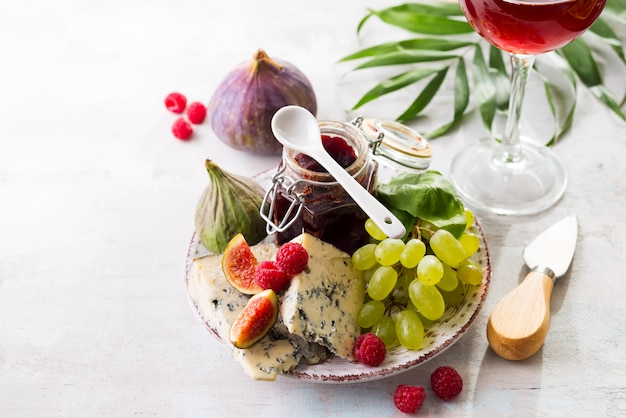 Assortment of cheese, berries and grapes with red wine in glasses. on stone