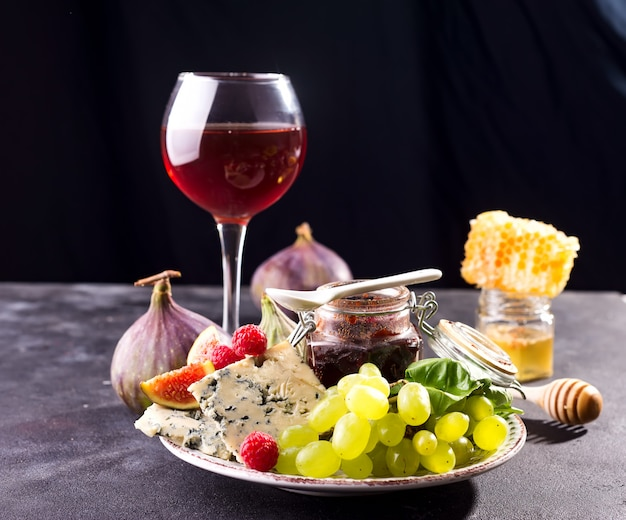 Assortment of cheese, berries and grapes with red wine in glasses on stone