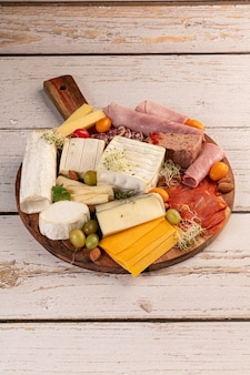 Assortment of cheese and cold meats on a wooden tray on a table