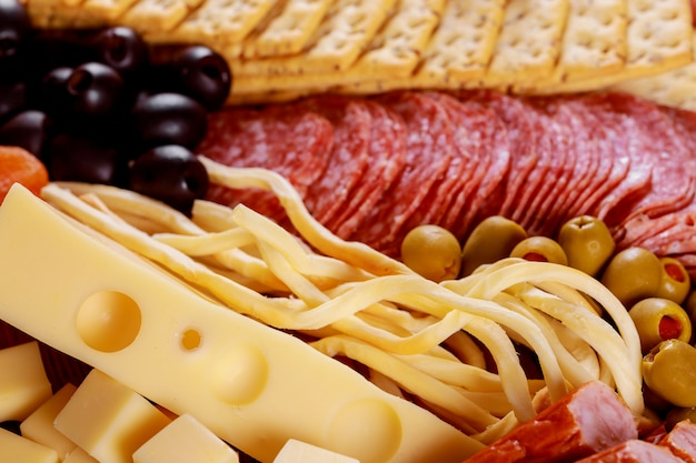 Assortment of cheese and olives on salami sausage table