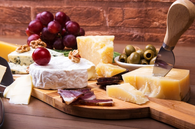 Assortment of cheese with fruits, grapes, nuts and cheese knife on a wooden serving tray