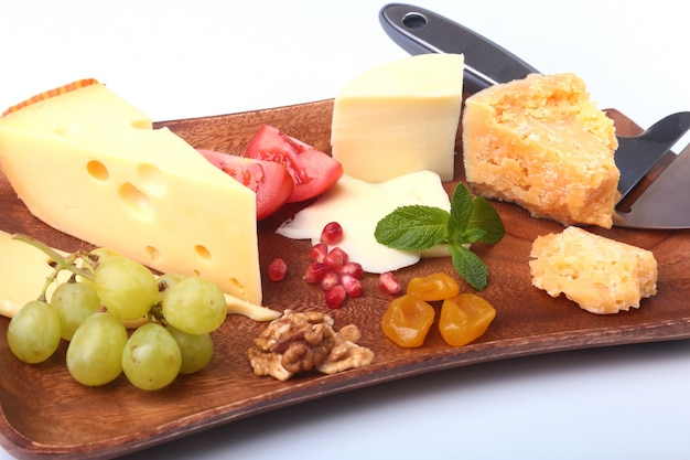 Assortment of cheese with fruits, grapes, nuts and cheese knife