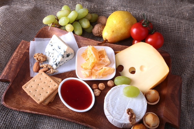 Assortment of cheese with fruits, grapes and nuts on a wooden serving tray.