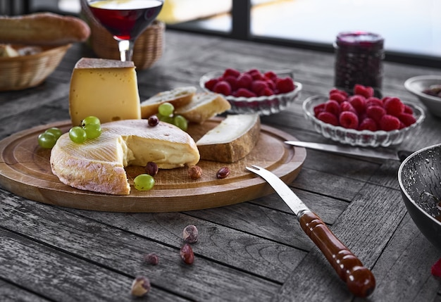 Assortment of cheese on a wooden tray with wine, on the table.