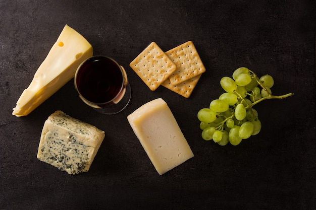 Assortment of cheeses and wine on black. top view