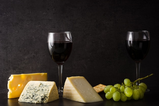 Assortment of cheeses and wine on black.