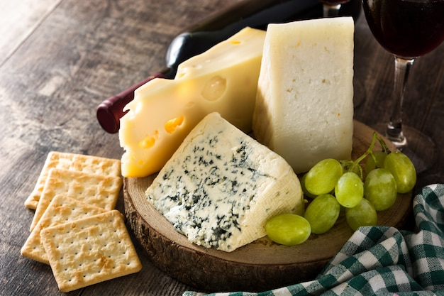 Assortment of cheeses and wine on wooden table. close up