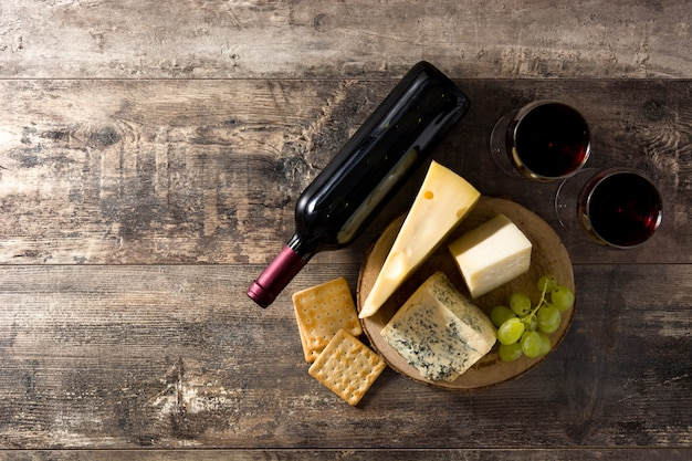 Assortment of cheeses and wine on wooden table. top view. copy space