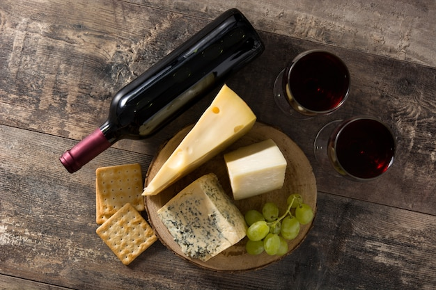 Assortment of cheeses and wine on wooden table. top view